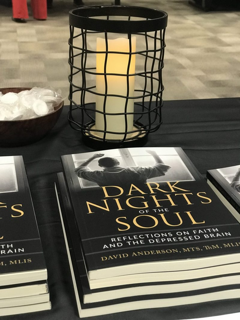 Book on display with candle behind