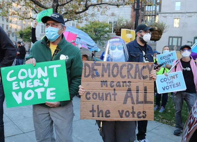 "Protesters with signs ""Count the Votes,"" ""Count every vote,"" ""Democracy means count all the votes."""