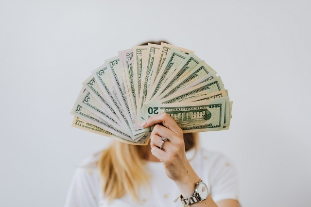 blond woman hiding face behind money